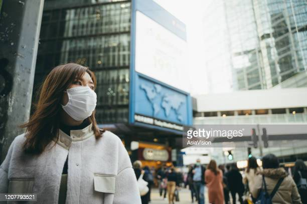 young asian woman wearing a protective face mask to prevent the spread of germs and viruses in the city - coronavirus stock pictures, royalty-free photos & images