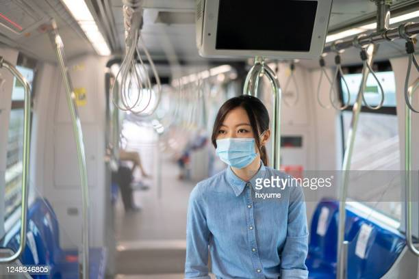 公共交通機関で仕事をするために通勤中にフェイスマスクを着用した若いアジアの女性 - バンコク・スカイトレイン ストックフォトと画像