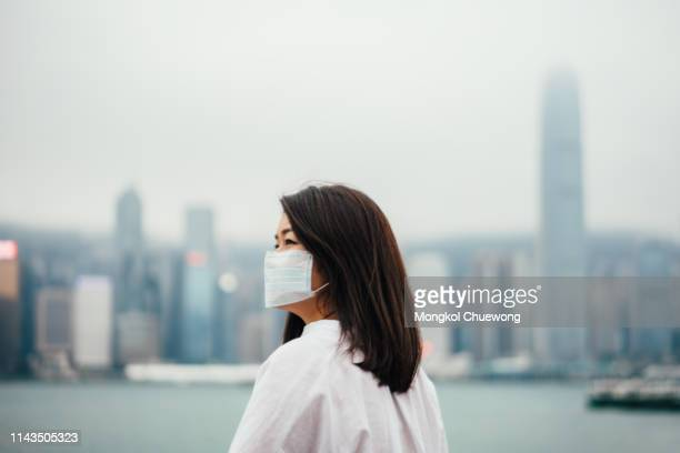 young asian woman wearing protective face mask in city due to the polluted air - virus bildbanksfoton och bilder