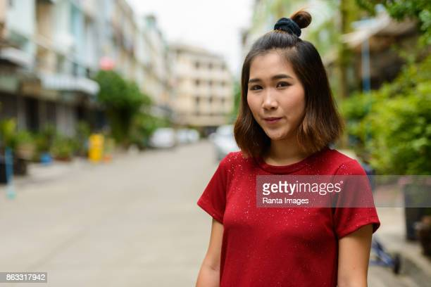 Young Asian woman wearing red shirt dress in the streets outdoors