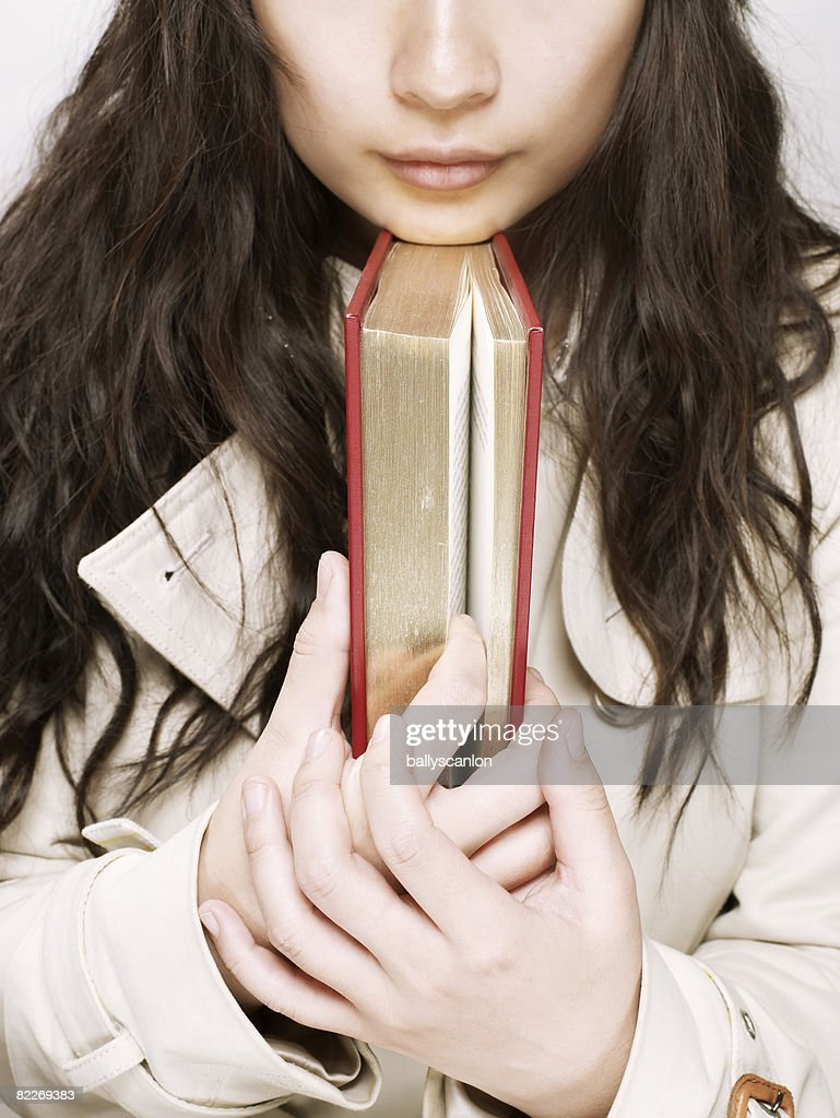 Young asian woman with a book under her chin : Stock Photo