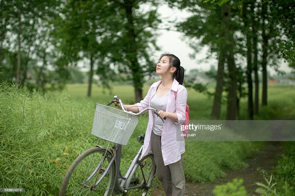 Young asian woman with bike on the country lane : Foto stock