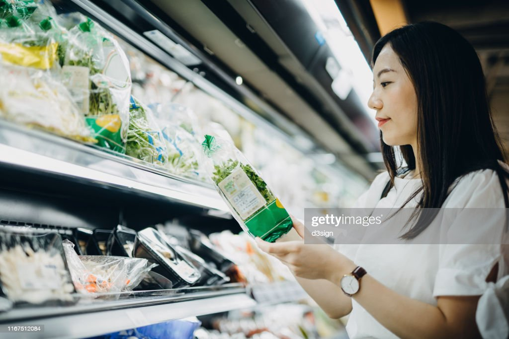 Young Asian woman with cart grocery shopping for fresh produce. She is shopping for fresh vegetables in a supermarket : Stock Photo