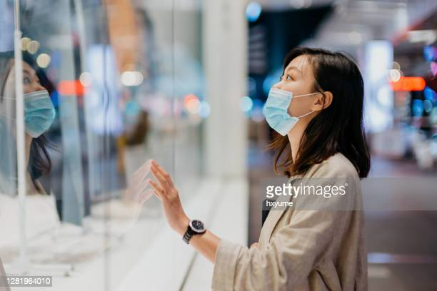 young asian woman with face mask looking at shop window while walking in the city at night - desire stock pictures, royalty-free photos & images