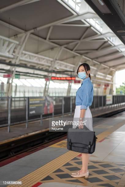 フェイスマスクを持つ若いアジアの女性がプラットフォームに立ち、ライトレールの輸送を待つ - バンコク・スカイトレイン ストックフォトと画像