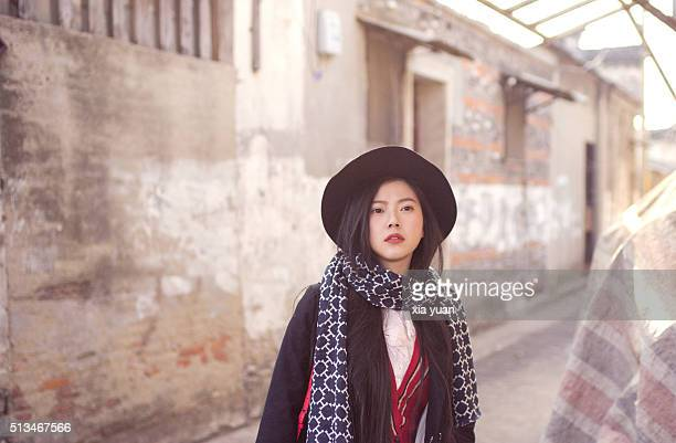 young asian woman with hat standing in an alley,looking away - yangzhou foto e immagini stock