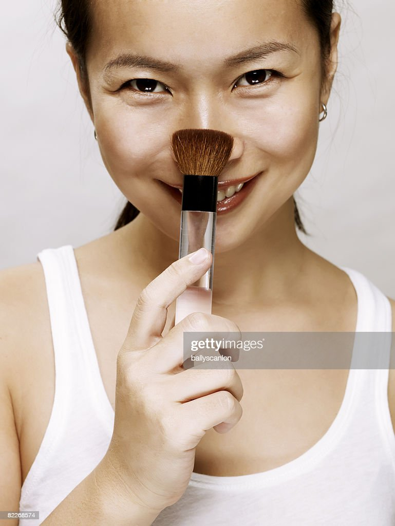young asian woman with makeup brush, smiling : Stock Photo