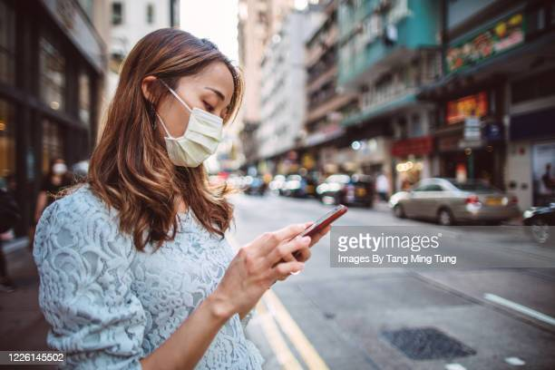 young asian woman with medical face mask using smartphone while exploring around in local city street - healthcare stock pictures, royalty-free photos & images