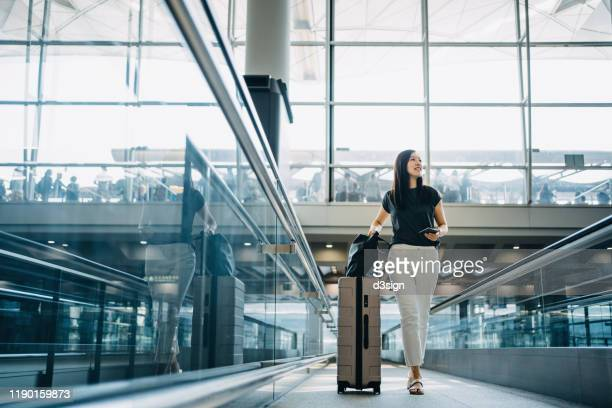 young asian woman with passport carrying suitcase walking in the airport concourse - 乗客 ストックフォトと画像