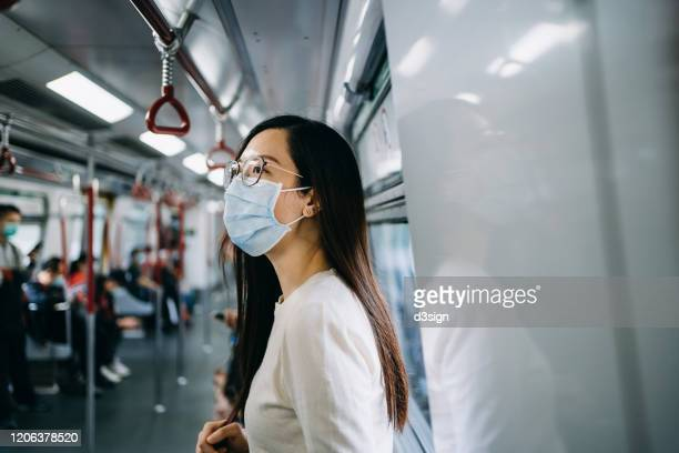young asian woman with protective face mask commuting in the city riding on subway - covid stock pictures, royalty-free photos & images