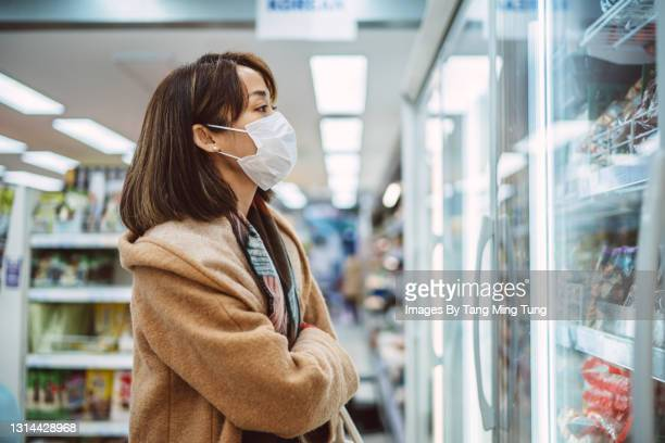 young asian woman with protective face mask doing grocery shopping for frozen food in supermarket - merchandise stock pictures, royalty-free photos & images