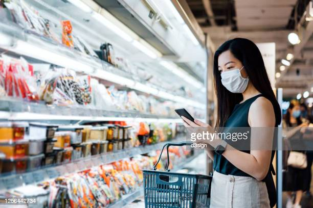 young asian woman with protective face mask holding shopping basket and using smartphone while grocery shopping in a supermarket - パンデミック ストックフォトと画像