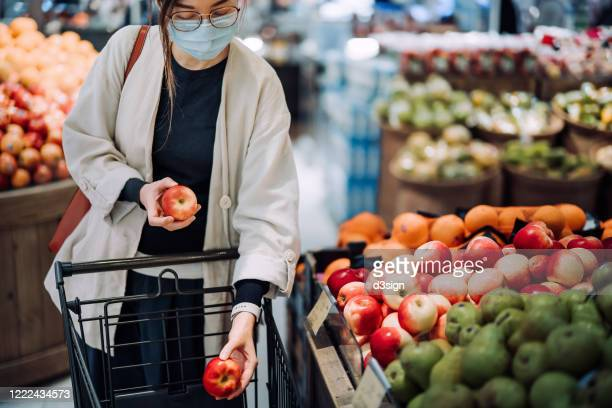 young asian woman with protective face mask shopping for fresh groceries in supermarket during the outbreak of covid-19 health crisis - state of emergency stock pictures, royalty-free photos & images