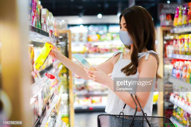 young asian woman with protective face mask with shopping cart basket in supermarket inside department store. asia girl doing grocery and choosing things to buy during covid-19 coronavirus pandemic - thai ethnicity stock pictures, royalty-free photos & images