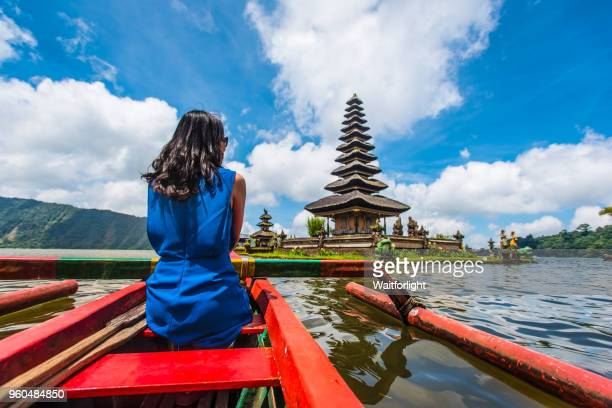 young asian woman with pura ulu danau temple under cloud sky,bali,indonesia - bali stock pictures, royalty-free photos & images