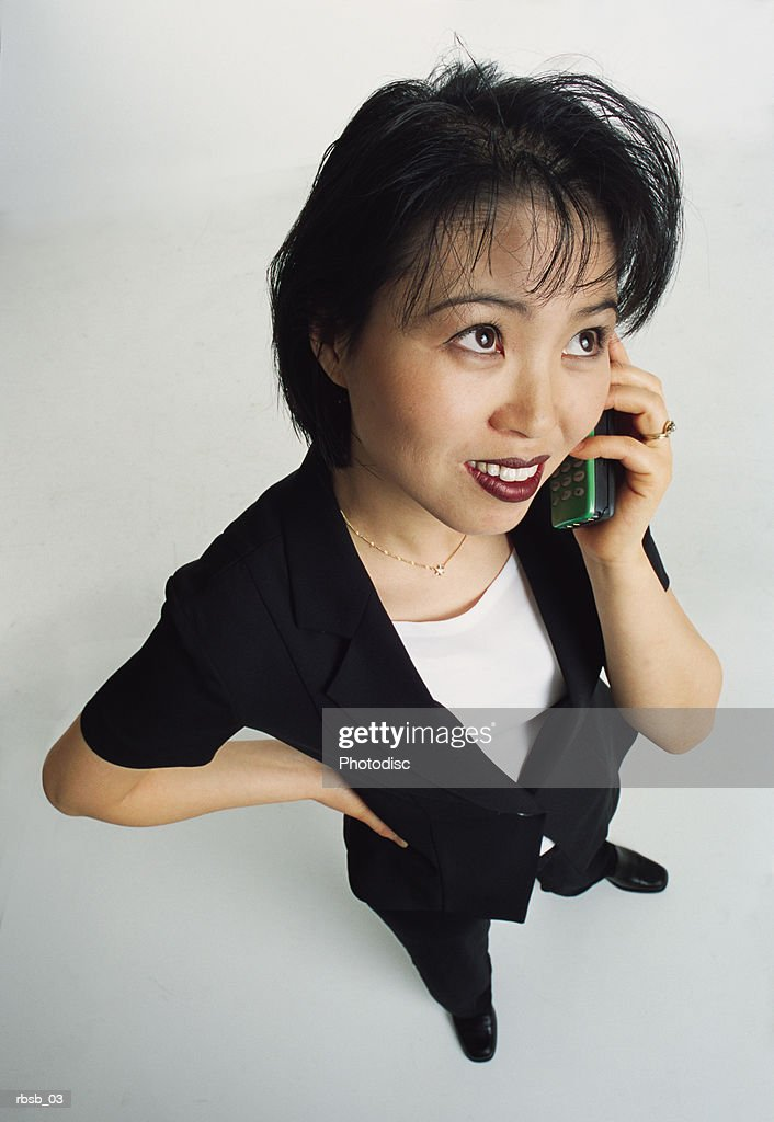 young asian woman with short dark hair in a dark suit talking into a cell phone : Foto de stock