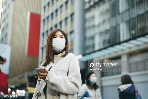 young asian woman with smartphone wearing a protective face mask to prevent the spread of germs and viruses in the city - china coronavirus stock pictures, royalty-free photos & images