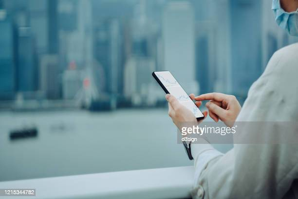 young asian woman with surgical face mask checking financial stock market analysis with a downward trend on smartphone due to the covid-19 health crisis, against hong kong city skyline - bankruptcy stock pictures, royalty-free photos & images