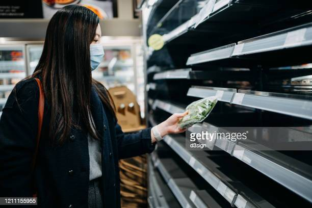 young asian woman with surgical face mask shopping for vegetables in front of empty shelves in a supermarket after panic buying due to the outbreak of coronavirus - panic buying stock pictures, royalty-free photos & images