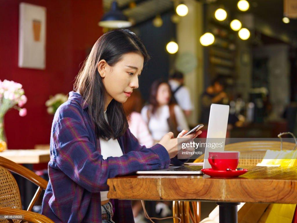 若いアジア女性コーヒー ショップを使用して、携帯電話パソコンでの作業 : ストックフォト