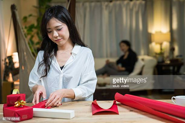 Young Asian Woman Wrapping a Gift