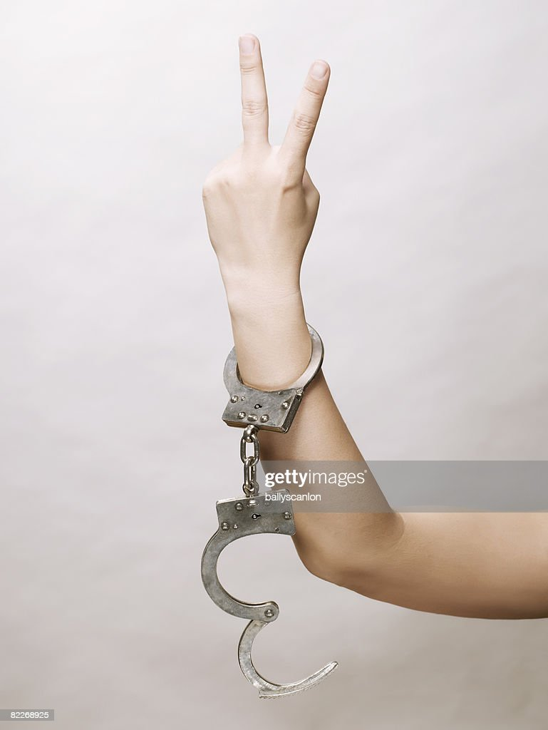 Young asian woman's arm with handcuffs : Stock Photo