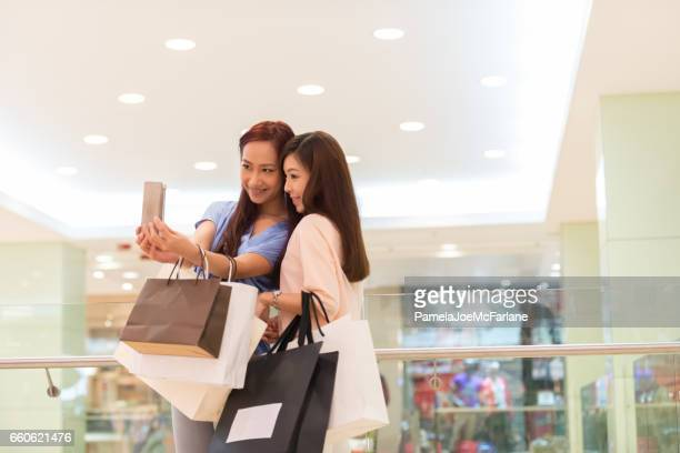 Young Asian Women Friends in Luxury Shopping Mall Taking Selfie
