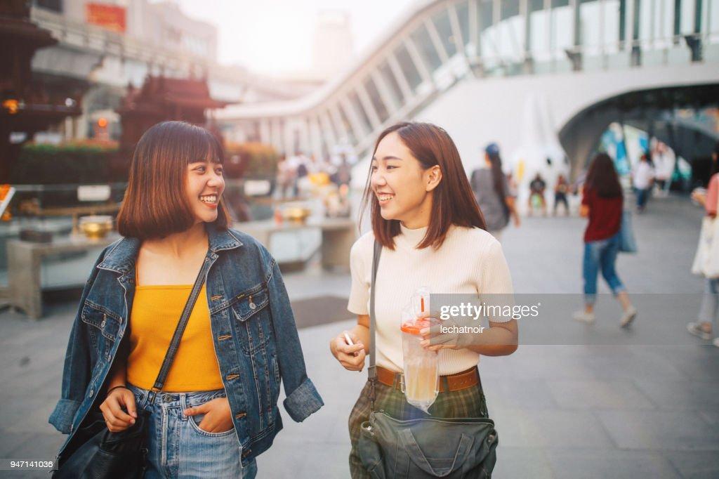 Junge asiatische Frauen in Bangkok gehen, gehen zusammen einkaufen, chatten : Stock-Foto