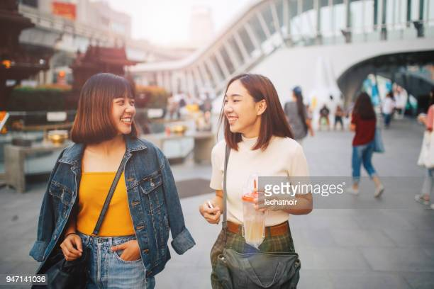 young asian women walking in bangkok, going shopping together, chatting - asian and indian ethnicities stock pictures, royalty-free photos & images