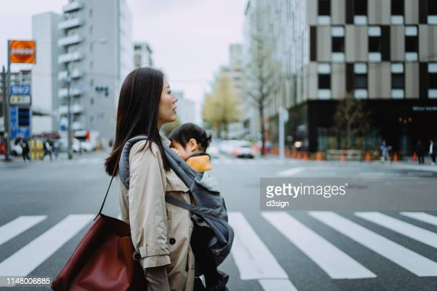 young asian working mother crossing street and commuting in busy downtown city with little daughter - working mother stock pictures, royalty-free photos & images