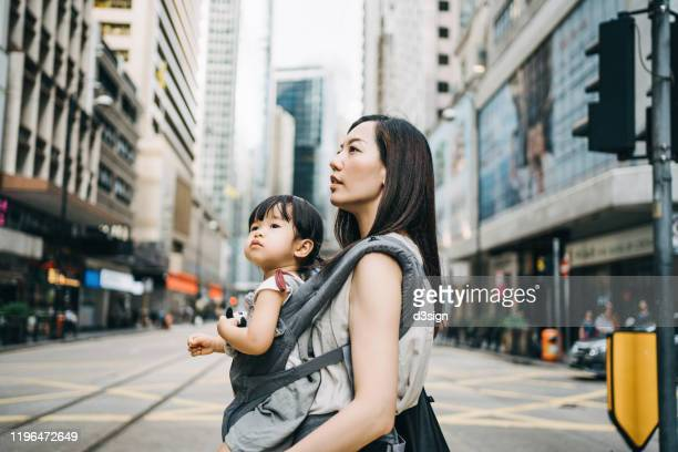 young asian working mother crossing street and commuting in busy downtown city with cute little daughter - prosperity stock pictures, royalty-free photos & images