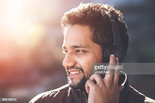 Young Asian/Indian man listening to music