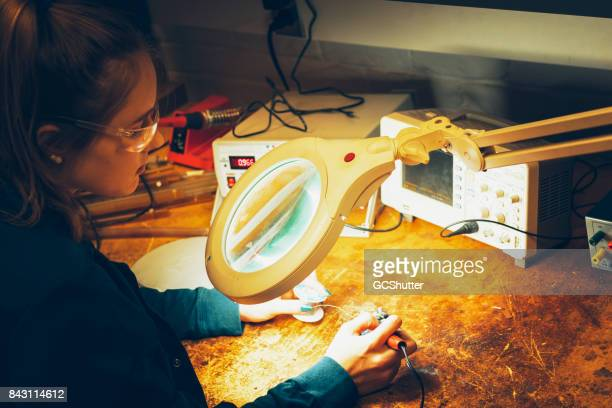 Jonge aspirant vrouwelijke ingenieur werken in een donkere electronics lab met een vergrootglas verlichting om te solderen een Printplaat