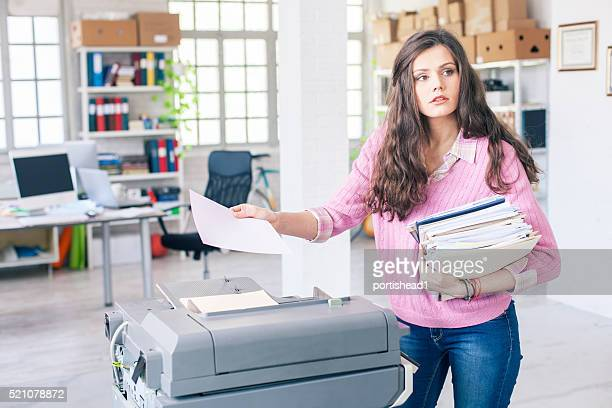 Young assistant using copy machine at workplace