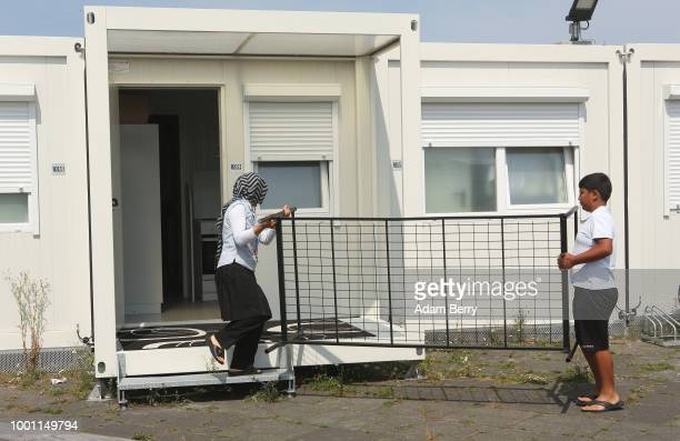 A pedestrian passes the entrance to a refugee reception center at the former Tempelhof airport on July 18 2018 in Berlin Germany Local politicians...