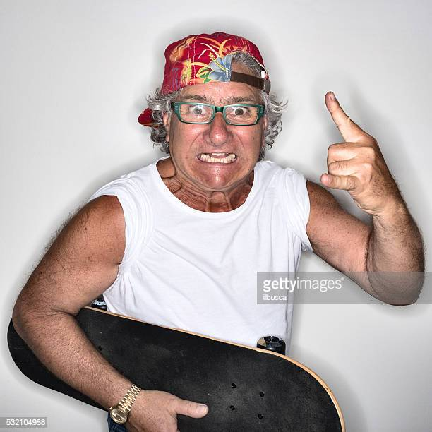 Young at heart grandpa with skateboard and rock and roll