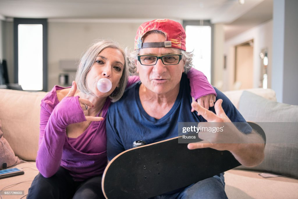 Young at heart grandparents: Rock and roll sign with skateboard and bubble gum : Stock Photo