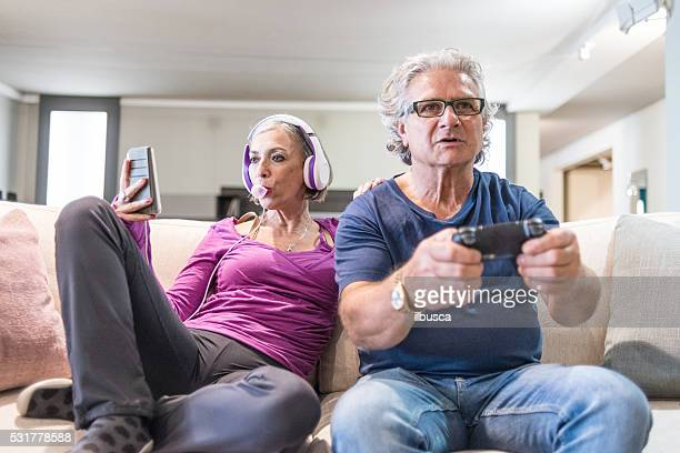 young at heart grandparents series: listening music and playing videogames - freaky couples stockfoto's en -beelden