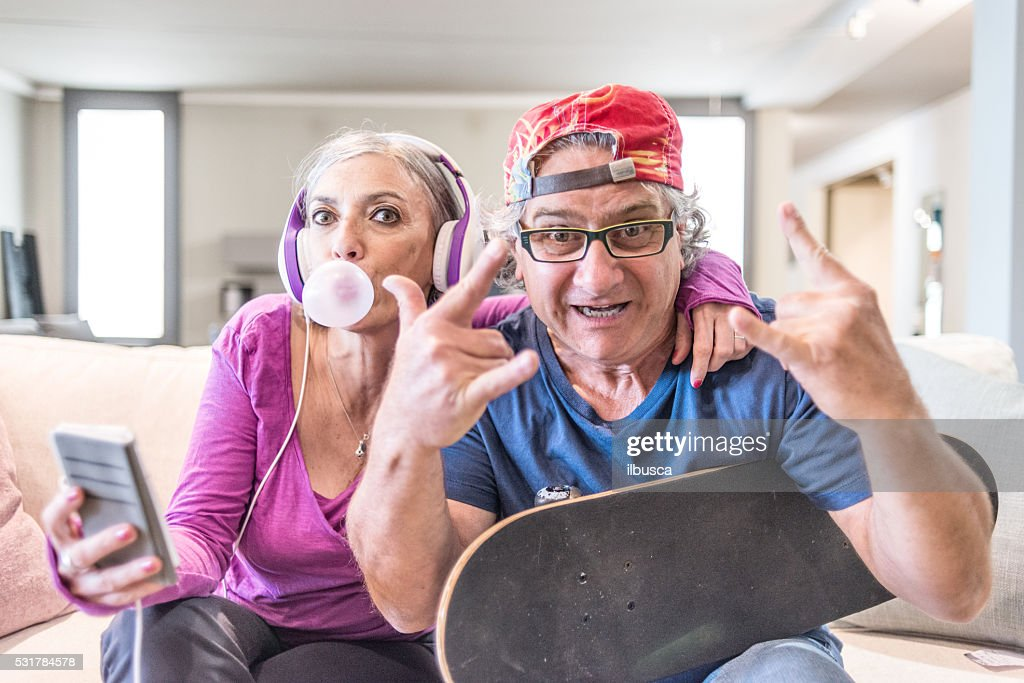 Young at heart grandparents series: Listening music and rock sign : Stock Photo