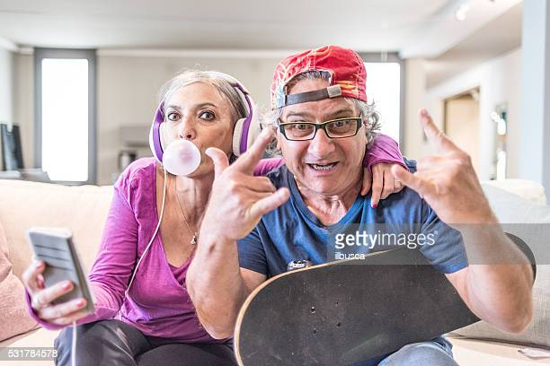 young at heart grandparents series: listening music and rock sign - freaky couples stockfoto's en -beelden