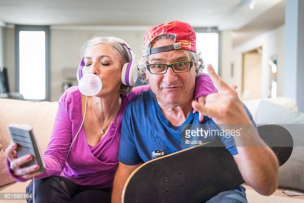 young at heart grandparents series: listening music and rock sign - freaky couples stock photos and pictures