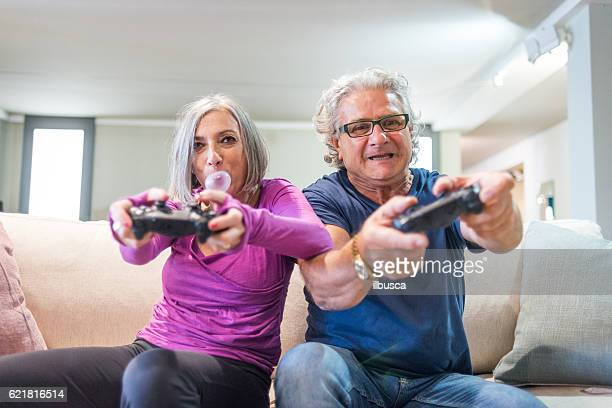 young at heart grandparents series: playing videogames - freaky couples stock photos and pictures