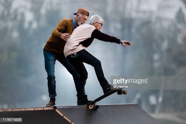 young at heart senior couple having fun at skate park. - active lifestyle stock pictures, royalty-free photos & images