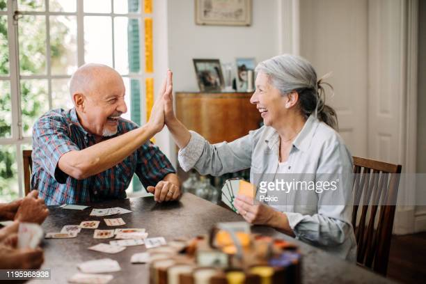 young at heart seniors having fun time in nursing home - poker card game stock pictures, royalty-free photos & images
