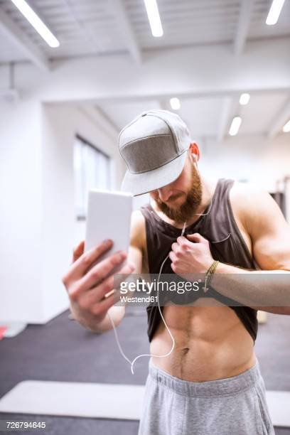 Young athete taking sixpack selfies in gym