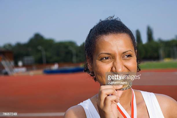 Young athlete biting her medal