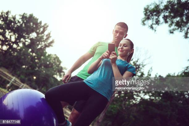 Young Athlete Couple Checking The Mobile App Infographic and Calories Count in Public Park