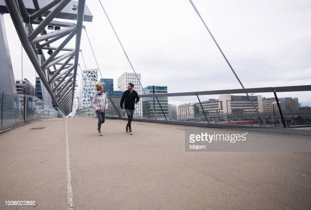young athlete couple jogging in city centre at sunset. - oslo stock pictures, royalty-free photos & images
