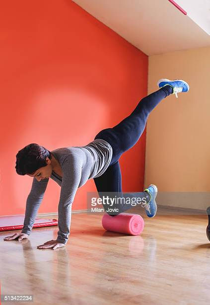 Young athlete doing pilates on support roller