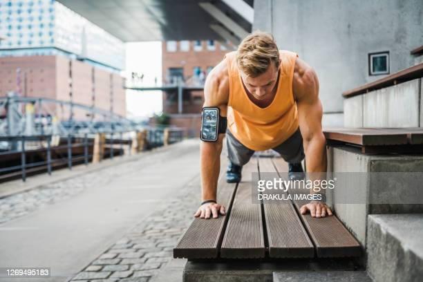 young athlete doing push ups on bench - 自重トレーニング ストックフォトと画像